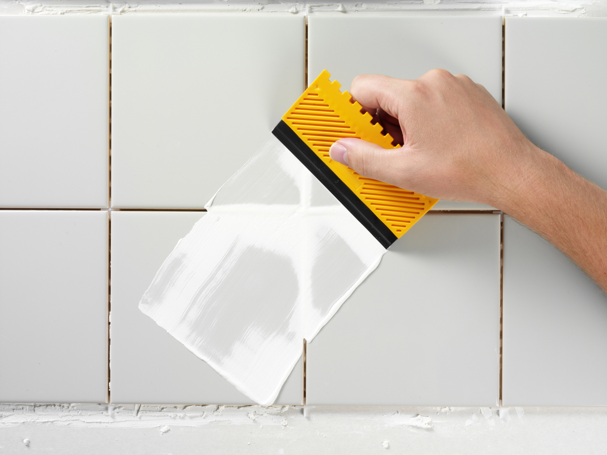 Applying grout with a spreader