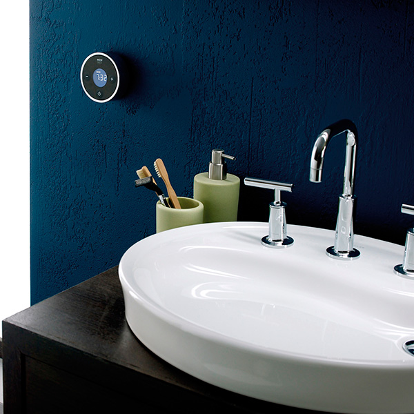 Bathroom sink with chrome taps and green toothbrush and soap pots