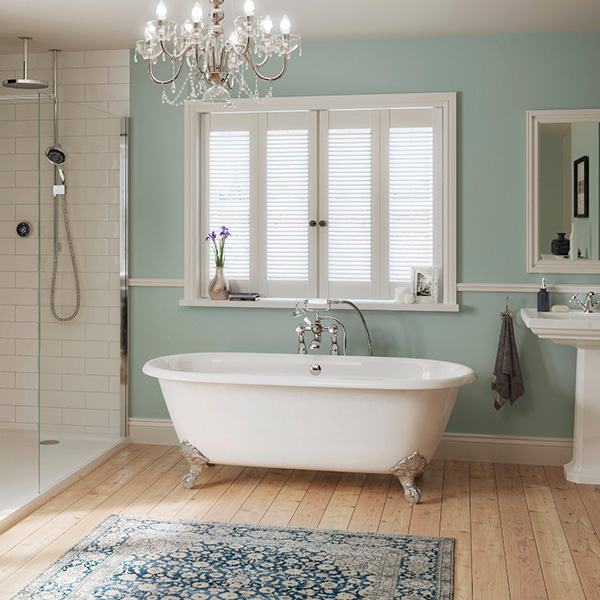 Bathroom with white shower room and white freestanding bath. pale green walls and vintage rug