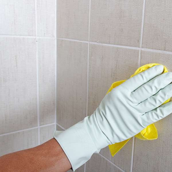 Rubber gloved hand cleaning bathroom grout on tiled wall