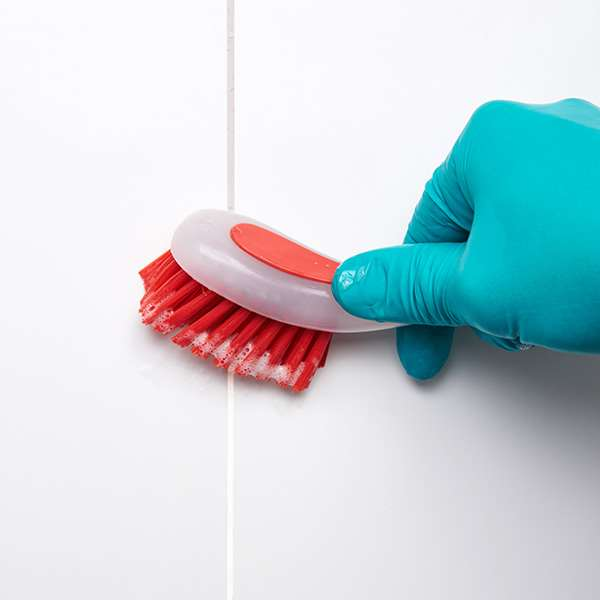Red brush cleaning grout on white tiled wall