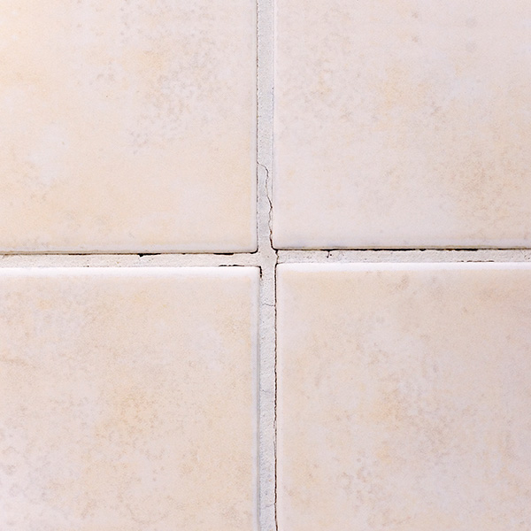 Cream tiles with old cracked grout